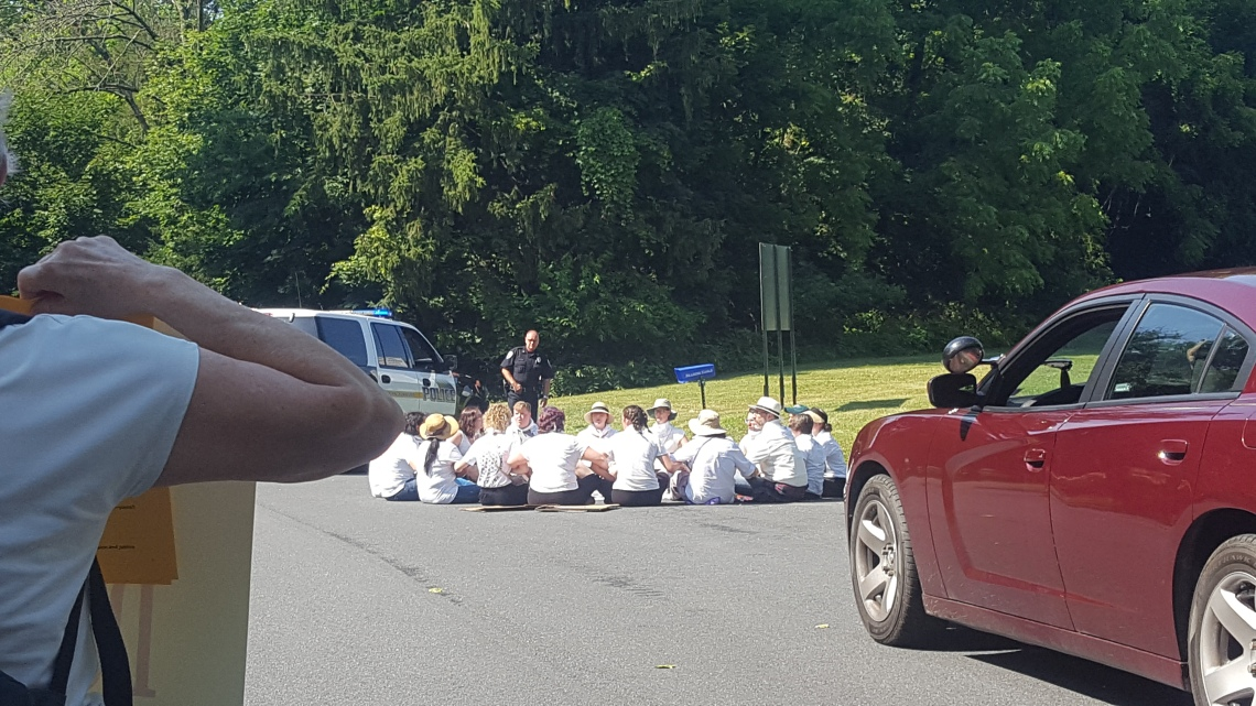 About 17 people sit in a circle in a road, with a police officer standing and looking at them
