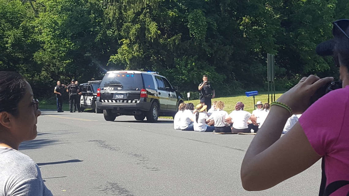 A police officer with a camera watches a group of people seated in a road, and several other officers stand nearby