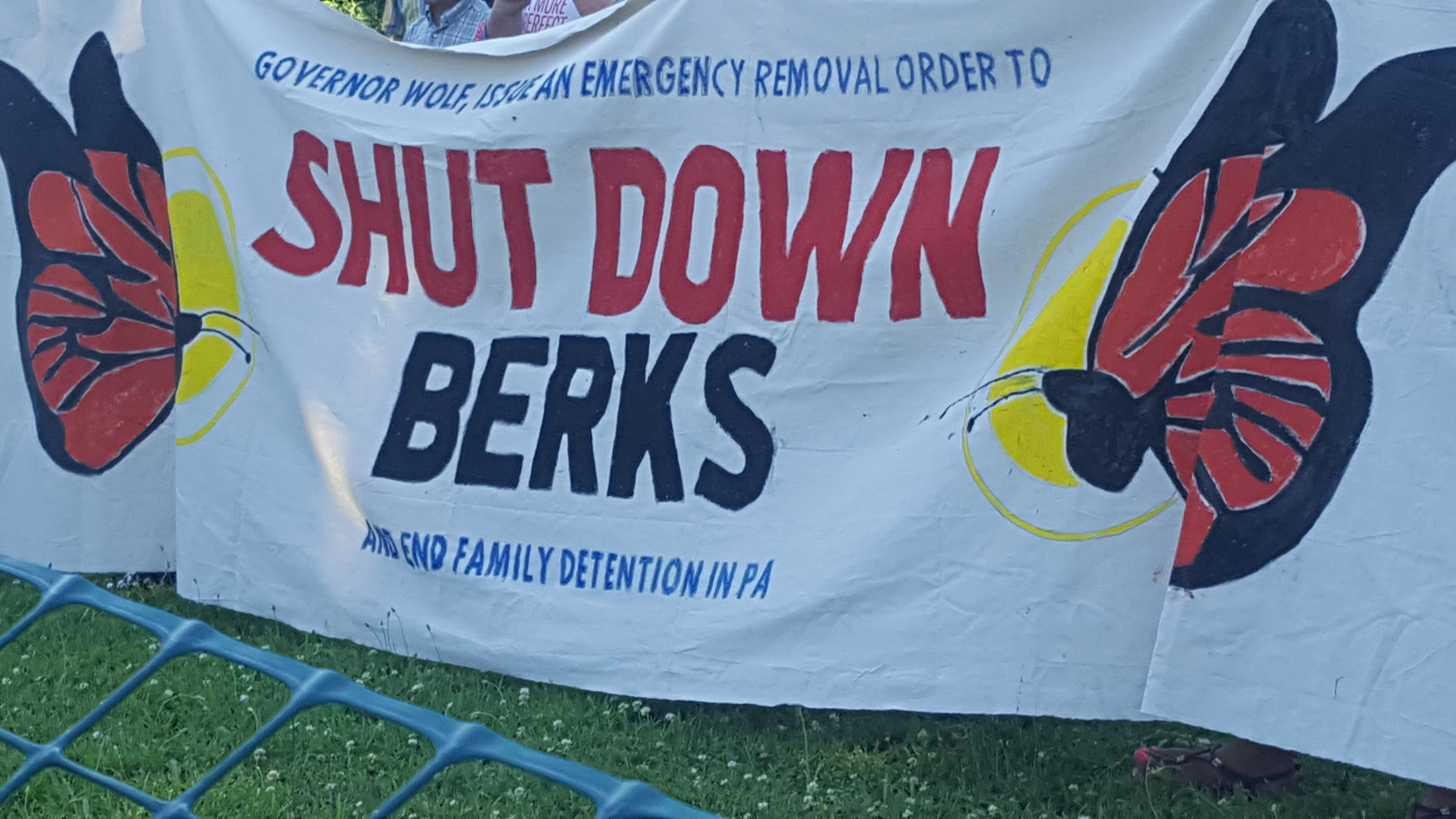 "[Image description: A banner with two butterflies reads: ""Governor Wolf, Issue an Emergency Removal Order to SHUT DOWN BERKS and end family detention in PA""]"