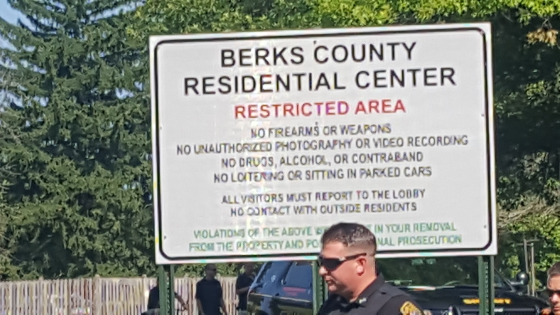 "A police officer walks past a sign that reads: ""Berks County Residential Center. Restricted Area. No firearms or weapons. No unauthorized photography or video recording. No drugs, alcohol, or contraband. No loitering or siting in parked cars. All visitors must report to the lobby. No contact with outside residents. Violations of the above will result in your removal from the property and potential criminal prosecution."""