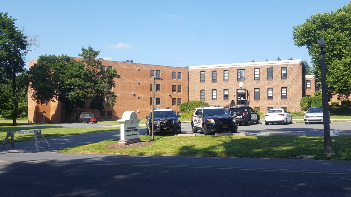 [Image description: A brown building with narrow windows and a parking lot with police cars]