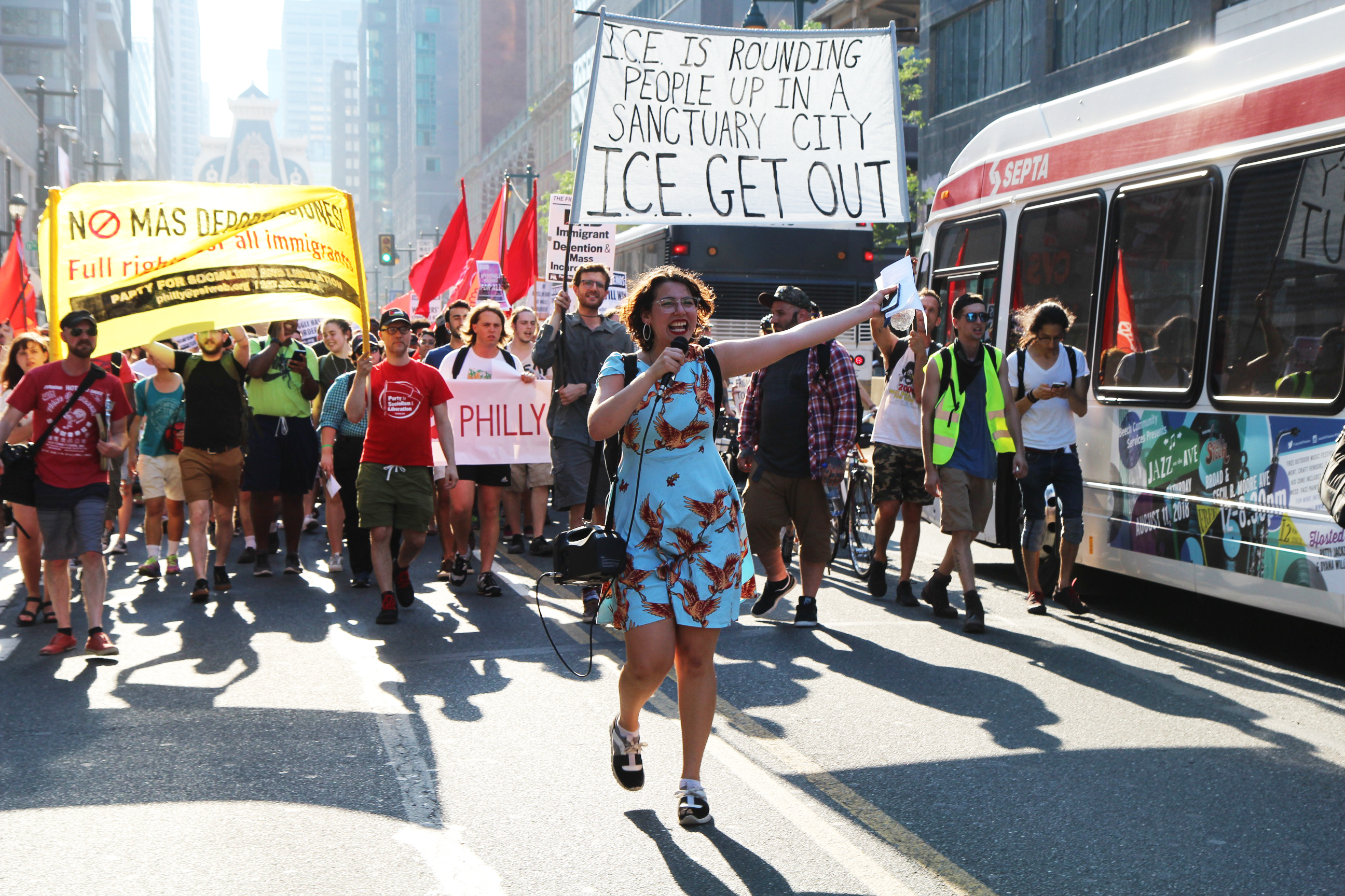 "Protesters march in the street, carrying a banner that reads ""ICE is rounding people up in a sanctuary city. ICE GET OUT."" An activist leads the march with a megaphone."