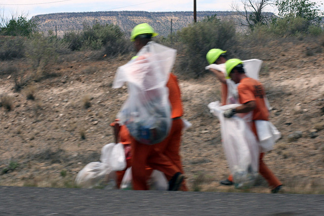 Incarcerated people in orange uniforms pick up trash by the side of a road.