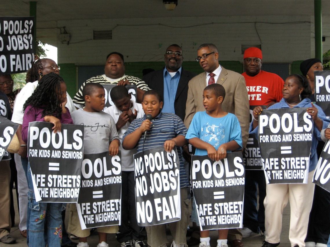 """Several children and adults stand holding signs that read """"Pools for kids and seniors = safe street for the neighbors"""" and """"no pools? no jobs? no fair!"""""""