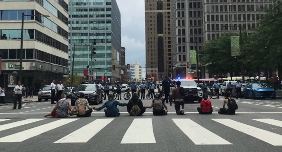 Eight people sit or kneel across an intersection with their hands linked, as police on bicycles and in police cars face them.
