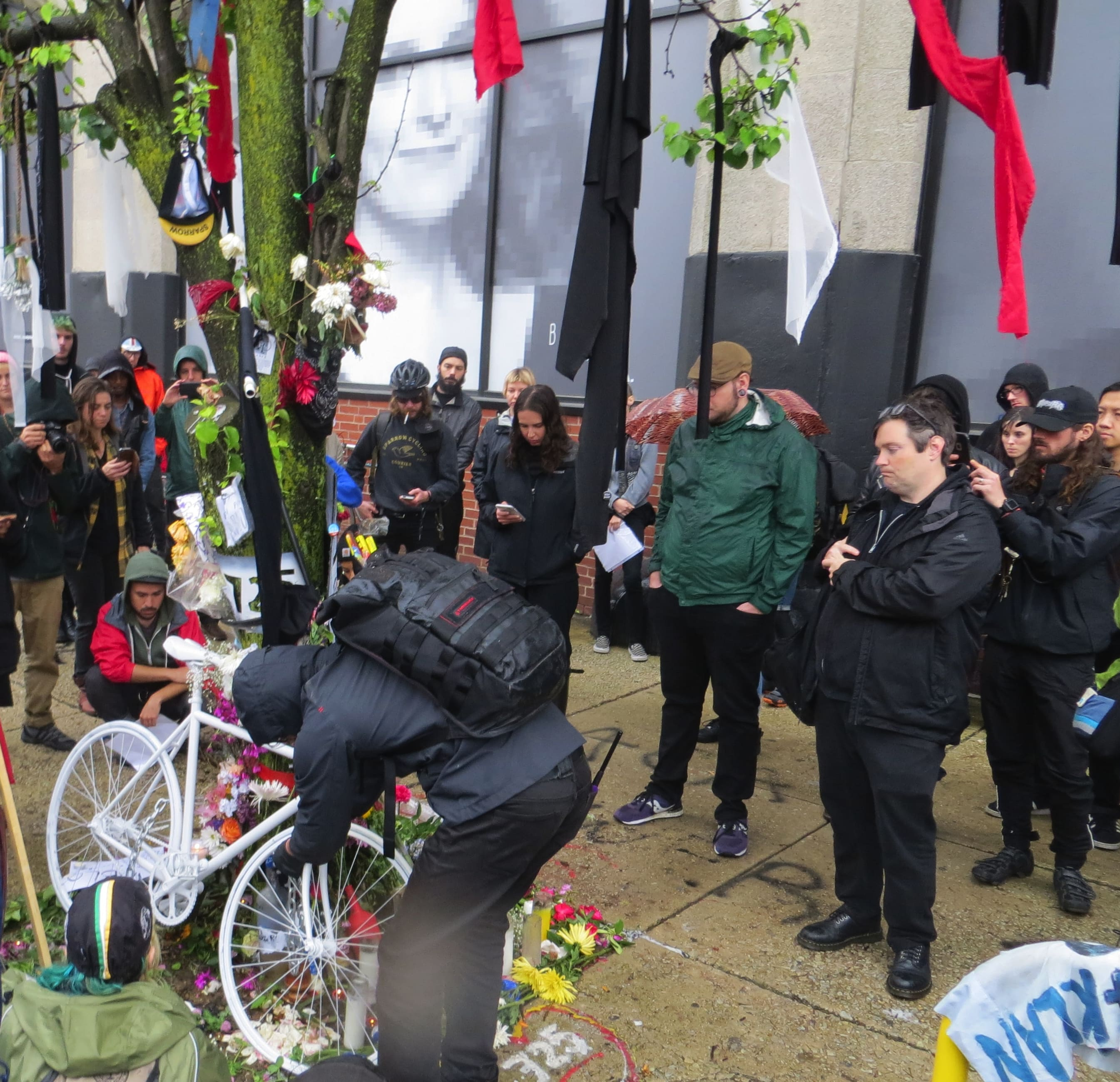 "Several dozen people gather around Pablo's memorial, at which a solid white ""ghost bike"" is being placed."