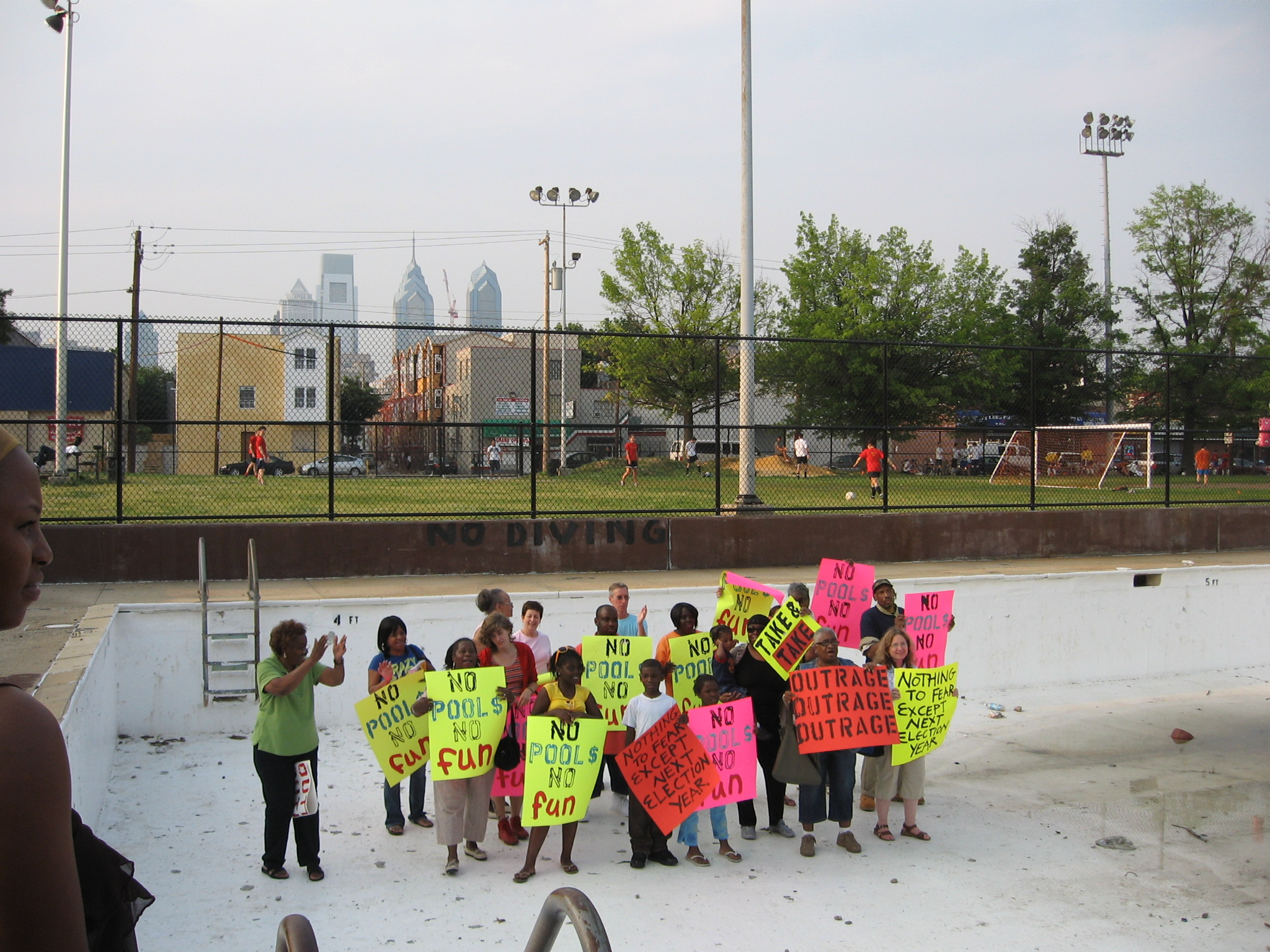 """About a dozen children stand in an empty swimming pool holding signs that read """"no pools, no fun."""""""