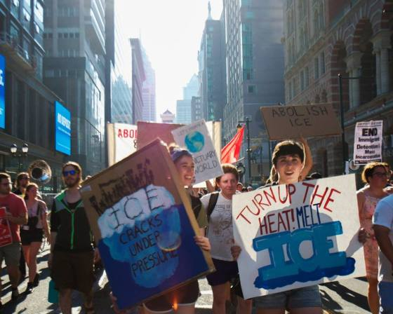 "Protesters hold signs that read ""Turn up the heat! Melt ICE"" and ""ICE cracks under pressure."""