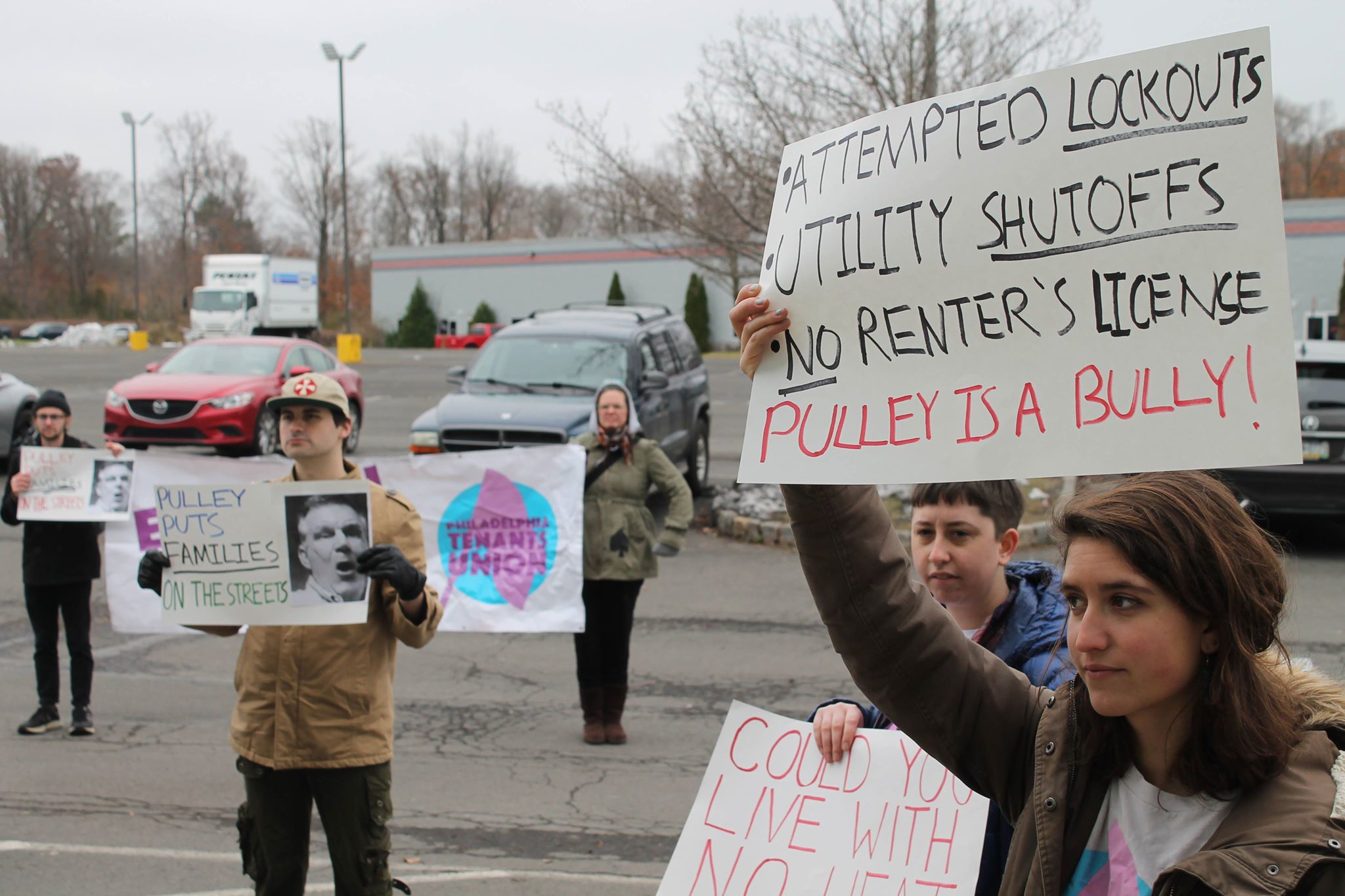 "Several activists stand in a parking lot. A sign reads ""Attempted lockouts, utility shutoffs, no renter's license, Pulley is a bully!"""